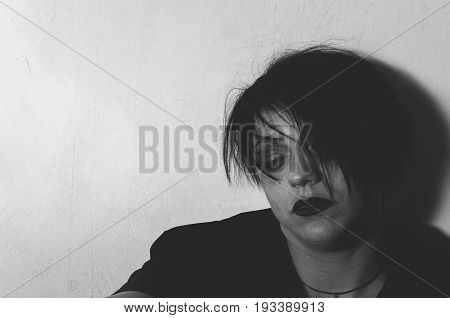 Depression. Depressed girl with black lipstick sitting alone in her room. Black and white. Loneliness. Sadness.
