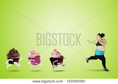 Diet concept. Scared overweight woman wearing sportswear and refuse to eat cupcakes by running to lose weight shot with green screen background