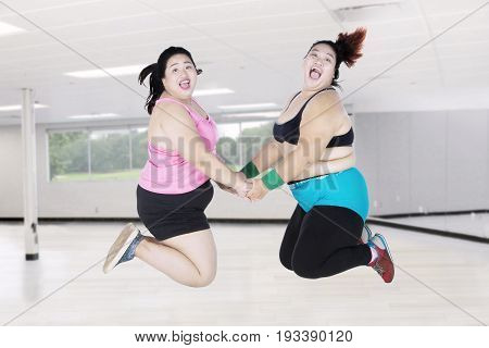 Two obese women leaping together in the gym while looking at the camera