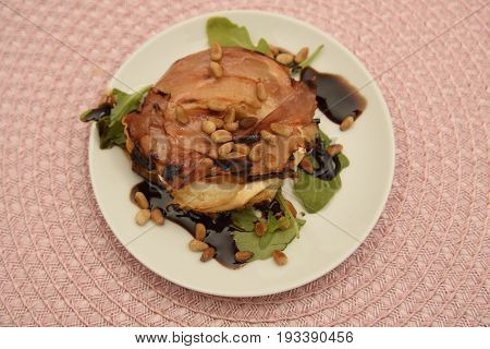 Starter with parma ham and chevre cheese on a bread with roasted nuts on top and basilica with balsamico vinegar on the bottom.