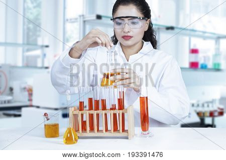Female scientist wearing glasses and doing biochemistry research with red and orange chemical liquid in the lab