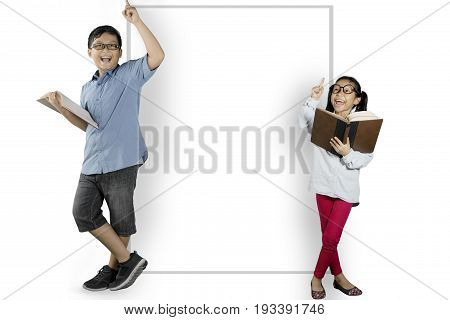 Two clever students reading a book while thinking an idea and leaning on a blank whiteboard