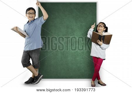 Two nerdy students holding a book while thinking an inspiration and standing near the blank chalkboard