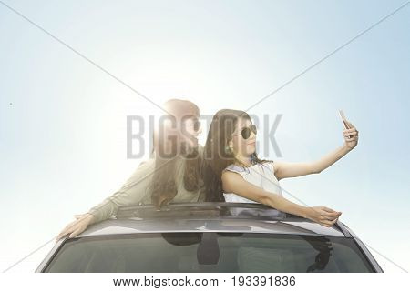 Two beautiful women using a smartphone to take a picture on the car roof with sunbeam on the background