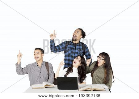 Young students get inspirations while pointing something together isolated on white background