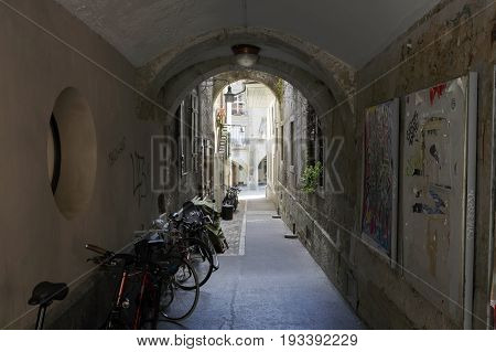 Bern Switzerland - April 20 2017: Narrow passage leads though the gate under the building from one street to another. Several parked bikes can be seen in the shaded gate