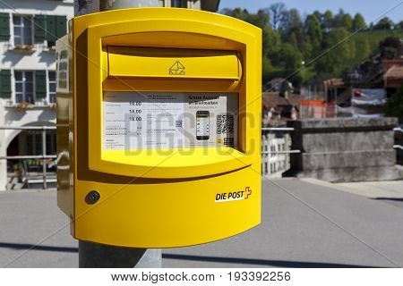 Bern Switzerland - April 21 2017: Painted yellow mailbox it is mounted on a pole in the old town and is a great help for many tourists to let them send a postcard while visiting the monuments
