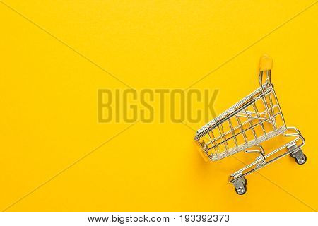 shopping trolley on yellow background. shopping trolley with some copy space. overturned shopping trolley. shopping trolley with yellow handle