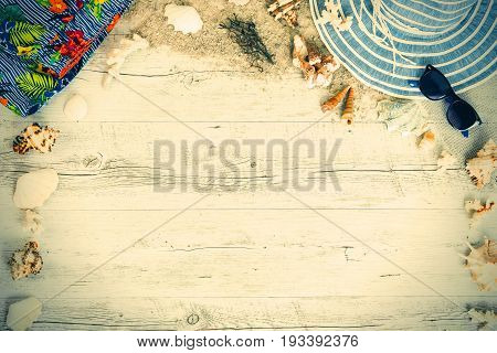 Sand and shells and hat on the wooden floor of the yelow summer concept travel Seychely beach Florida Hawai swim in Bali summer pradise