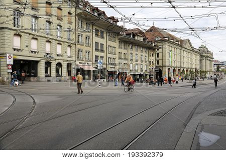 Bern Switzerland - April 17 2017: Buildings by a street in the old town and there are several people visible. On the roadway you can see the tram rails and the dense power grid is above.