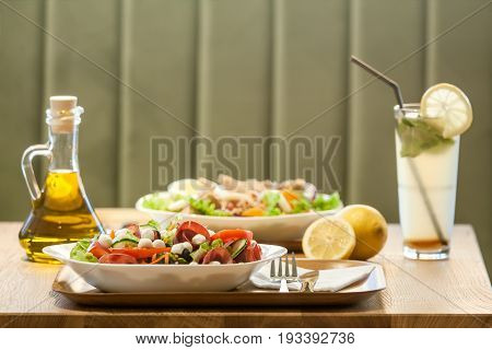 Two salads with ham meat tomatoes mozzarella lemon juice and olive oil bottle