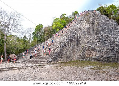 Coba Mexico - April 20 2016: Archaeological site touists climbing the Nohoch Mul pyramid