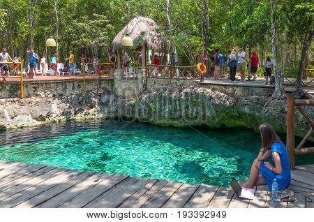 Coba Mexico - April 20 2016: Tourists bathing in the sinkhole of the archaeological site