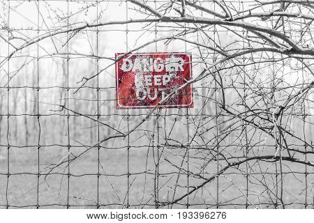 Red Danger Sign Posted To Barbed Fence Tangled In Branches, Warning People To Keep Out