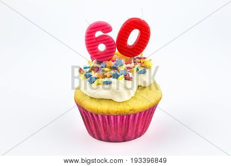 Cupcake with number sixty - 60 - pink candles with white vanilla frosting and colour star sprinkles in pink paper case isolated on white background - female birthday background with space for text