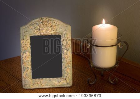 Decorative blank photo frame with lit candle on dresser - concept of love and memory