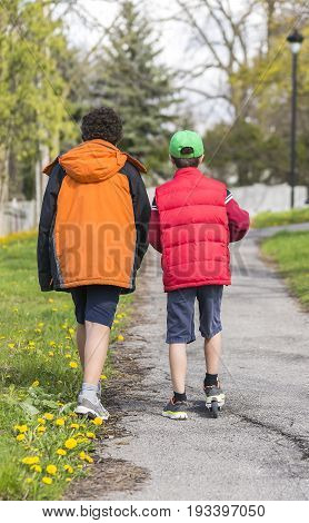 Two Boys Walking On A Path, One On A Scooter