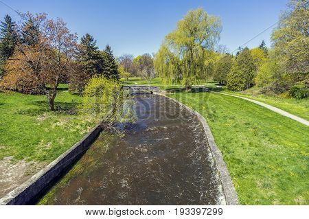 River Flowing Through Beautiful Parkland With Large Trees And Grassy Areas