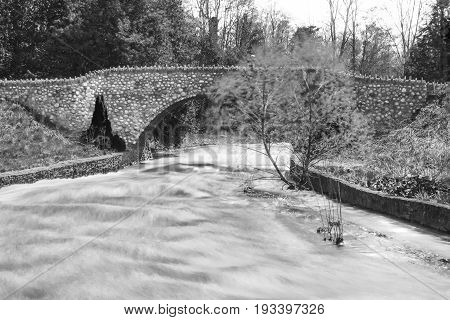 Swift River Water Moving Under A Stone Bridge Arch