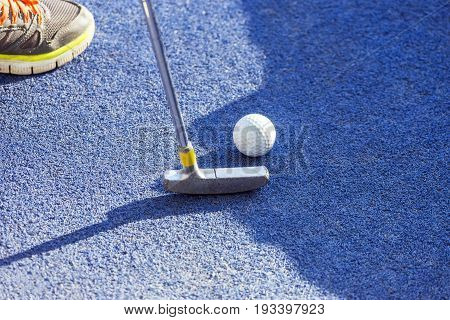 Closeup of putter and ball on mini golf course shoe of young boy player in top corner
