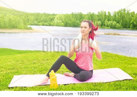 Young Attractive Fit Woman Resting After Workout Sport Exercises In Park On A Background Of Lake
