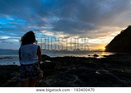 EL NIDO, PALAWAN, PHILIPPINES - MARCH 29, 2017: Wide angle view of a girl enjoying the sunset at Las Cabanas Beach.