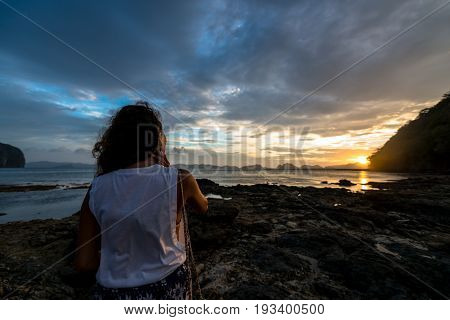 EL NIDO, PALAWAN, PHILIPPINES - MARCH 29, 2017: Wide angle view of a woman looking the sunset at Las Cabanas Beach.