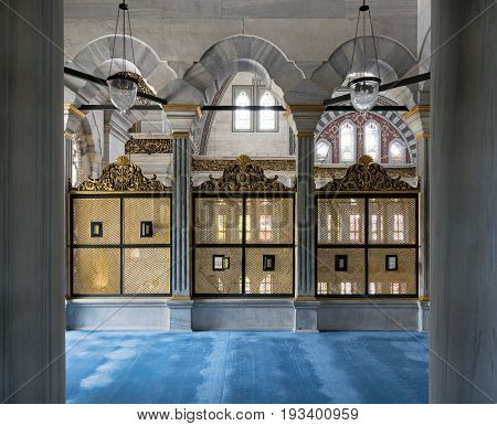 Istanbul, Turkey - April 20, 2017: Three gold painted decorated Interleaved wooden windows (Mashrabiya) framed by three marble arches, marble wall and blue carpet on the terrace of Nuruosmaniye Mosque
