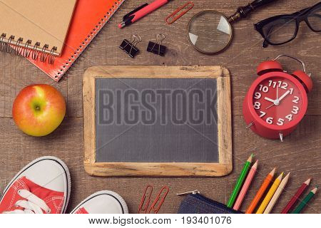 Back to school background with school supplies over wooden board. Top view. Flat lay