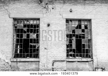 Old rustic facade of abandoned building with broken windows. Exterior wall of abandoned building. Black and white.