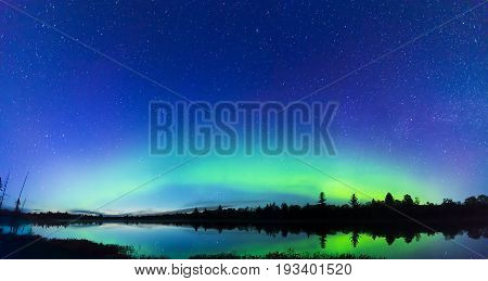 Panoramic Scene Of Northern Lights Arching And Glowing Over Silhouetted Landscape, Blue Sky Full Of