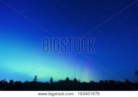 Blue Northern Night Sky Full Of Stars With Soft Glow Of Northern Lights On Horizon