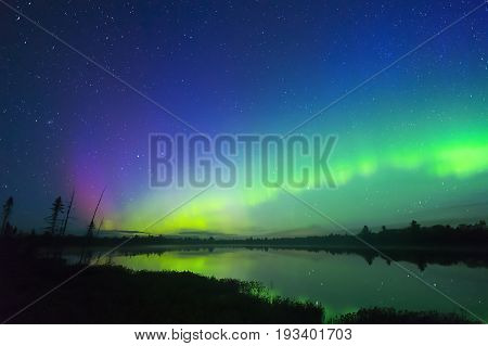 Beautiful Northern Lights Glowing In Waves Above Northern Night Landscape, Sky Full Of Stars