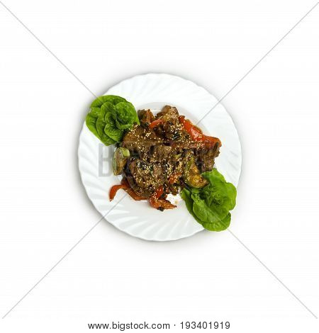 Veal with vegetables. juicy slices of veal with grilled vegetables under a spicy sauce, sesame emphasizes a symphony of aftertaste on the white plate isolated