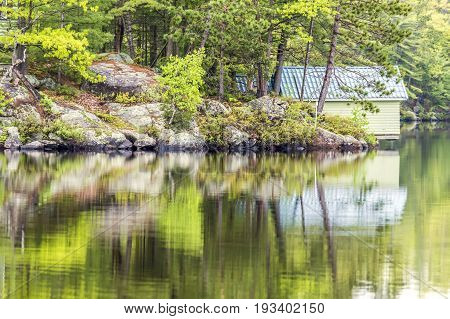 Rocks Of Canadian Shield And Forest Pine Trees Reflecting In Water