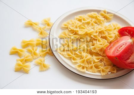 raw farfalle pasta with vegetables on plate