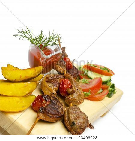close up duck shish kebabs with frit potatoes and fresh vegetables isolated