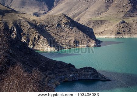 The picturesque lake in the mountain gorge between slopes. blue water, rest at a reservoir, the nature of the North Caucasus. mountain landscape