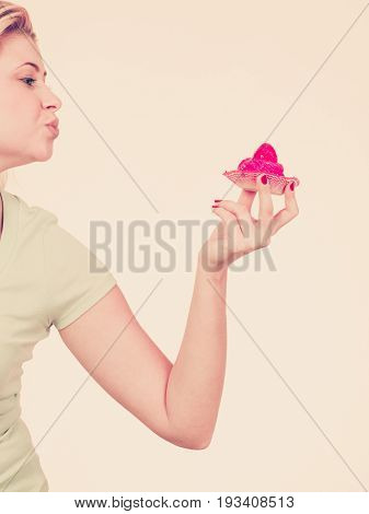 Sweets fat food sugar concept. Woman hand holding sweet strawberry cupcake sending air kisses.