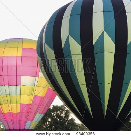 Contrasting hot air balloons ready to ascend at the 4th Annual Freedom Aloft Balloon Rally in Prineville in Central Oregon on a summer morning.