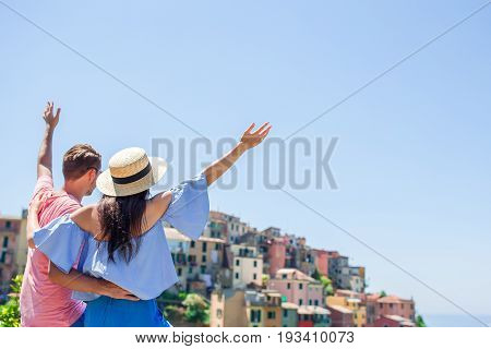 Young beautiful girl making with hands heart shape on the old coastal town background of Corniglia