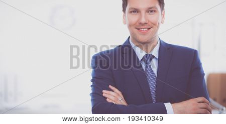 Business man or manager standing against his desk at office with  arms folded