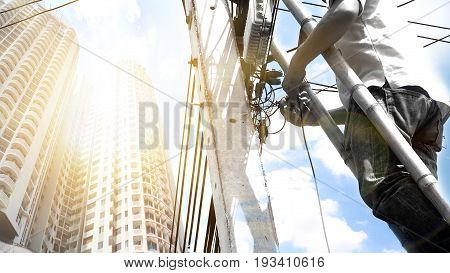 Electronics technician he climbing the bamboo stairs to install internet fiber optic has buiding under the sun light Man is black and white photo crop at working and lens flare technique at left is copy space.
