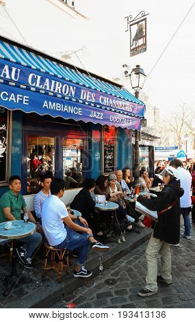 PARIS , France- June 01, 2017: View of typical paris cafe in Paris. Montmartre area is among most popular destinations in Paris, Au clairon de chasseur is a typical cafe.