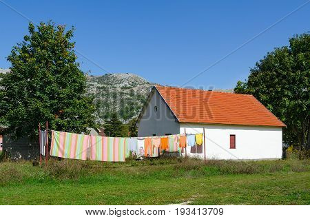 Village of Negushi in mountainous area Montenegro. Bed linen and clothes is dried on ropes near one-storey village house