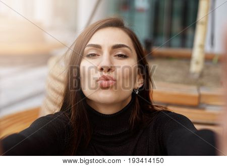 Outdoor portrait of beautiful student girl wearing black turtleneck sweater posing for selfie making duck face pouting sending kisses to friends via social networks. People and technology