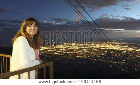 ALBUQUERQUE, NEW MEXICO, JUNE 18. The Sandia Peak Aerial Tramway Observation Deck on June 18, 2017, in Albuquerque New Mexico. A Woman on the Sandia Peak Aerial Tramway Observation Deck in Albuquerque, NM, Just After Sunset.