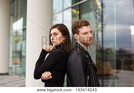 People love and relationships problem concept. Angry sad young European male and female standing on street back to back not looking at each other after conflict argument quarrel of fight