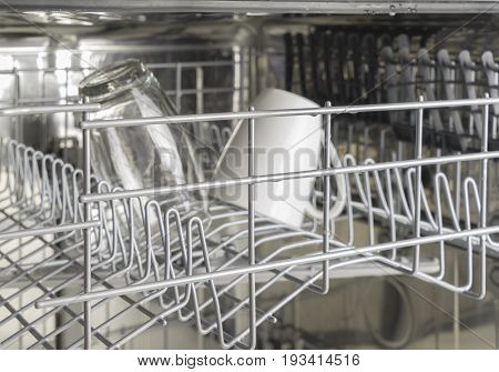 Washed glass and white mug in the dishwasher, the interior of the top rack of a dishwasher, selective focus, low depth field