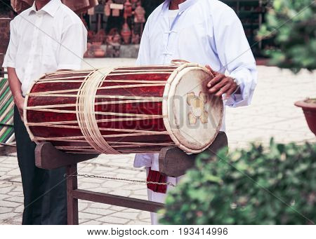 Vietnamese drum. The musician holds the drum and plays it